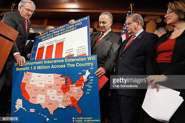 Sen Tom Harkin gets a hand with his posters from Sen Charles Schumer as Sen Robert Menendez and Sen Amy Klobuchar look on during a news conference...