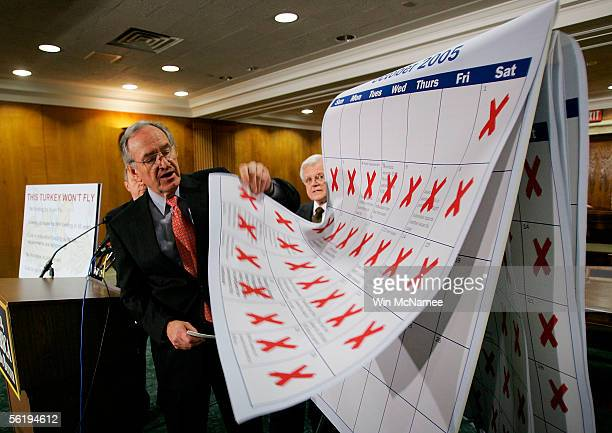 Sen Tom Harkin lifts pages of a calendar he said represented inaction on the part of the Bush administration during a press conference highlighting...