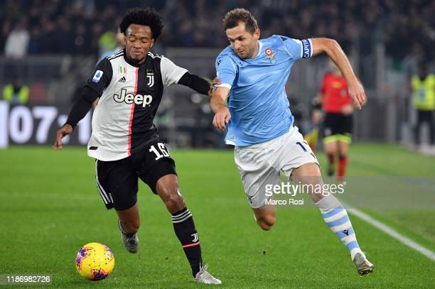 Senad Lulic of SS Lazio compete for the ball with Juan Cuadrado of Juventus during the Serie A match between SS Lazio and Juventus at Stadio Olimpico...