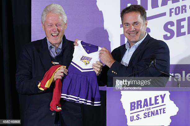 S Senate Democratic candidate Rep Bruce Braley gives former President Bill Clinton baby clothes with state university colors for his new...