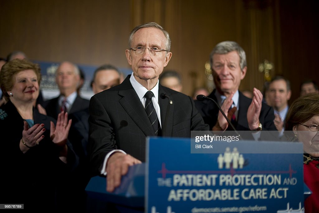 Senate Democrats clap as Senate Majority Leader Harry Reid, D-Nev., speaks at a news conference following a series of procedural votes on health care reform on Wednesday afternoon, Dec. 23, 2009.