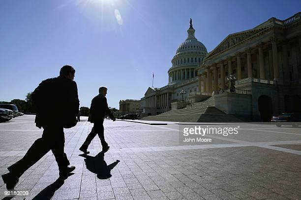 Senate Finance Chairman Max Baucus walks from his office to the Capitol as his senior advisor Scott Mulhauser runs to catch up October 21 2009 in...