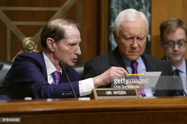 Senate Finance Committee Chairman Orrin Hatch and ranking member Sen Ron Wyden talk while hearing testimony from US Secretary of Commerce Wilbur Ross...