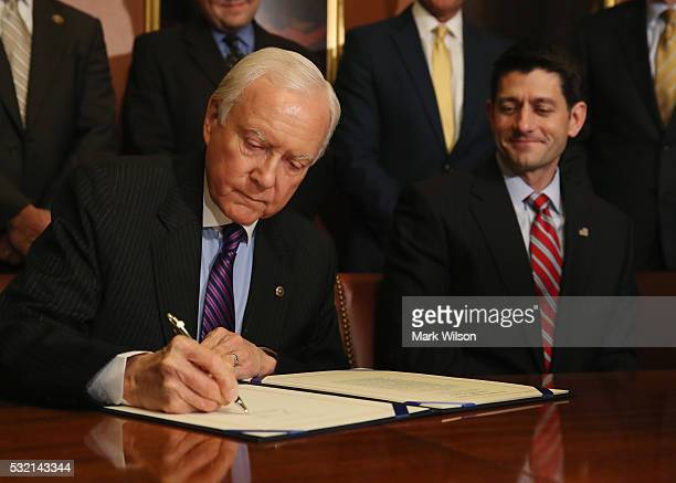 Senate Finance Committee Chairman Orrin Hatch is flanked by House Speaker Ryan while signing the American Manufacturing Competitiveness Act of 2016...
