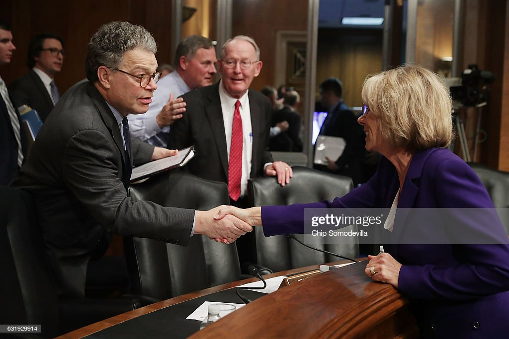 Senate Health, Education, Labor and Pensions Committee member Sen. Al Franken (D-MN) (L) shakes hands with Betsy DeVos, President-elect Donald Trump's pick to be the next Secretary of Education, with Sen. Michael Bennet (D-CO) after her confirmation hearing in the Dirksen Senate Office Building on Capitol Hill January 17, 2017 in Washington, DC. DeVos is known for her advocacy of school choice and education voucher programs and is a long-time leader of the Republican Party in Michigan.