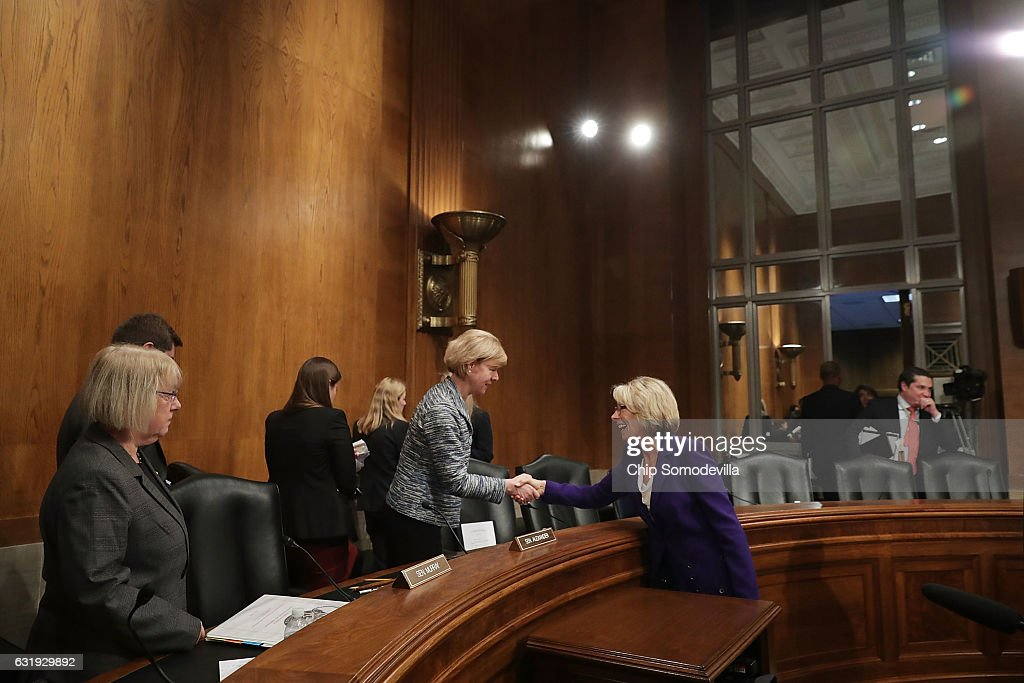 Senate Health, Education, Labor and Pensions Committee member Sen. Tammy Baldwin (D-MN) (L) shakes hands with Betsy DeVos, President-elect Donald Trump's pick to be the next Secretary of Education, with Sen. Michael Bennet (D-CO) after her confirmation hearing in the Dirksen Senate Office Building on Capitol Hill January 17, 2017 in Washington, DC. DeVos is known for her advocacy of school choice and education voucher programs and is a long-time leader of the Republican Party in Michigan.