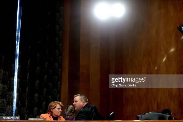 Senate Homeland Security and Governmental Affairs Committee members Sen Heidi Heitkamp and Sen John Tester talk during a hearing in the Dirksen...