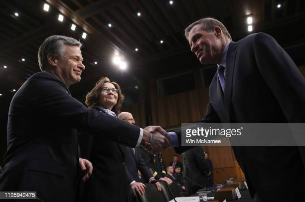 Senate Intelligence Committee Ranking Member Sen Mark Warner shakes hands with Christopher Wray director of the Federal Bureau of Investigation as...