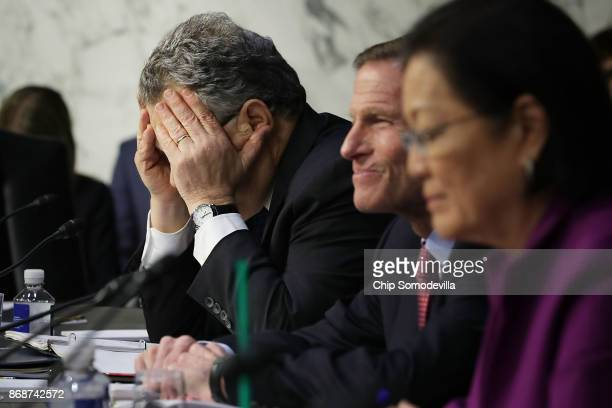 Senate Judiciary Committee member Sen Al Franken covers his face in frustration as he questions witnesses from Google Facebook and Twitter during a...