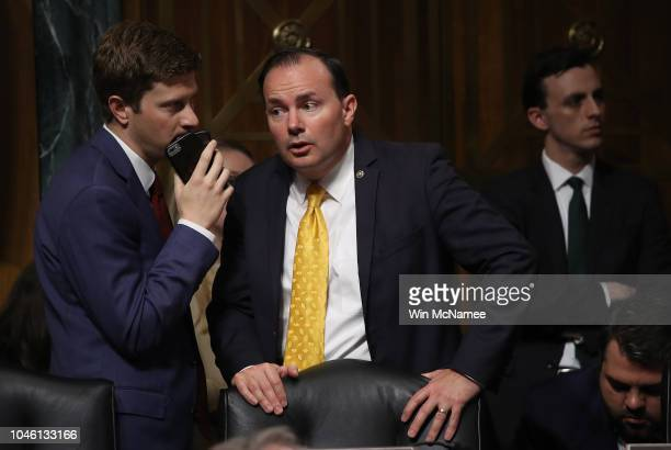 Senate Judiciary Committee member Sen Mike Lee confers with an aide during a committee meeting while Sen Jeff Flake was conferring with Democratic...