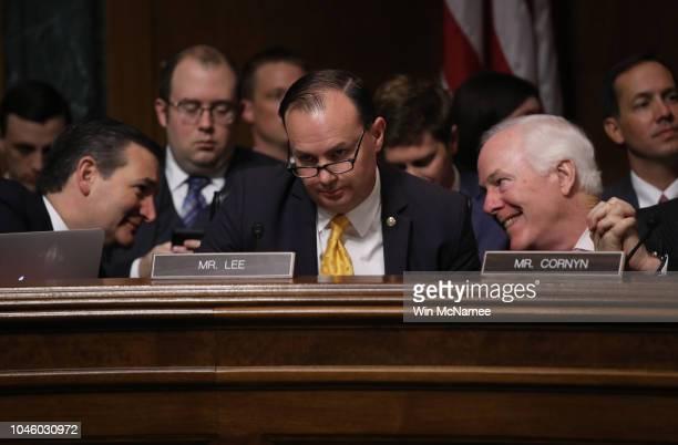 Senate Judiciary Committee members Sen Ted Cruz and Sen John Cornyn confer behind Sen Mike Lee during a committee meeting on September 28 2018 in...