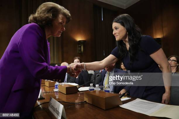 Senate Judiciary Committee ranking member Sen Dianne Feinstein greets 1996 Olympic Gold Medalist Dominique Moceanu before she testifies to the...