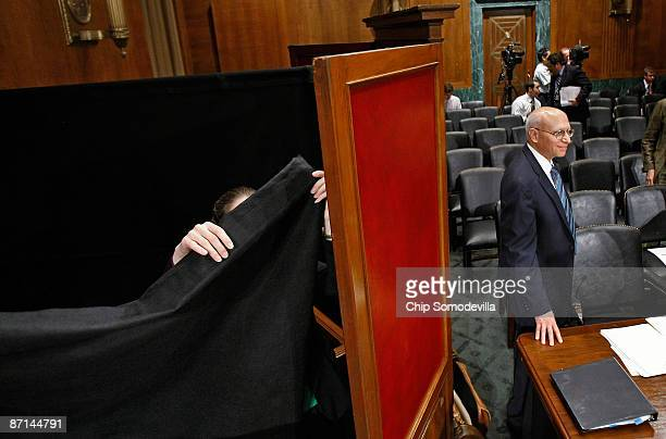 Senate Judiciary Subcommittee On Administrative Oversight and the Courts staff member raises a black curtin around a desk set aside for witness Ali...