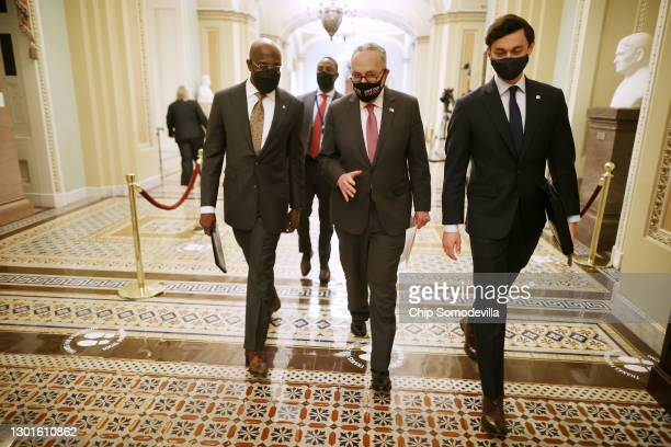 Senate Majority Leader Charles Schumer walks with Sen. Raphael Warnock and Sen. Jon Ossoff on their way to a news conference at the U.S. Capitol on...
