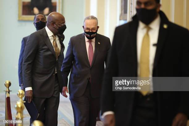 Senate Majority Leader Charles Schumer walks with Sen. Raphael Warnock on their way to a news conference at the U.S. Capitol on February 11, 2021 in...