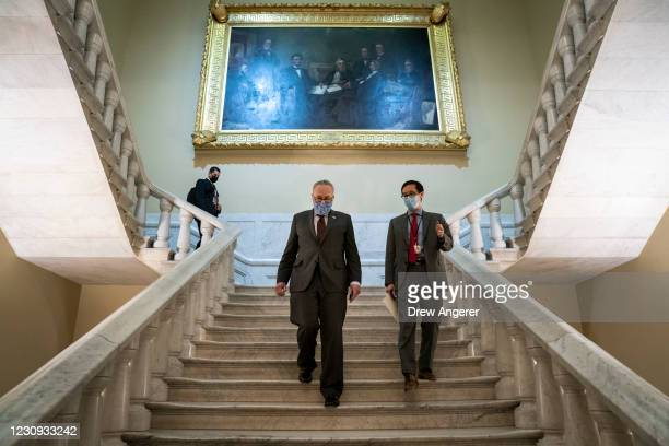Senate Majority Leader Chuck Schumer and an aide walk back to his office after a press conference at the U.S. Capitol on February 2, 2021 in...