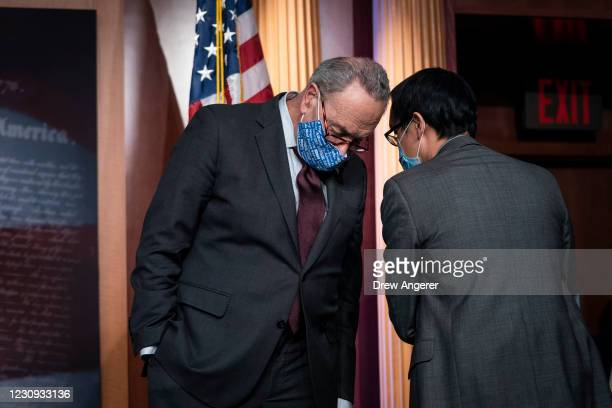 Senate Majority Leader Chuck Schumer confers with an aide during a press conference after a meeting with Senate Democrats at the U.S. Capitol on...