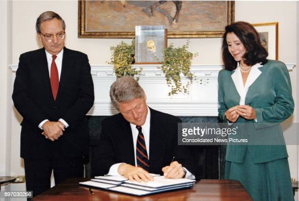 Senate Majority Leader George Mitchell and US Representative Nancy Pelosi watch as American politician US President Bill Clinton signs an executive...