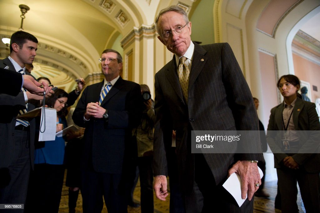 Senate Majority Leader Harry Reid, right, tries to pull Sen. Kent Conrad, D-N. Dak., away from reporters as they head to the podium for their official news conference following the Senate Democrats' lunch meeting with President Barack Obama to dicuss the budget in the U.S. Capitol on Wednesday, March 25, 2009.