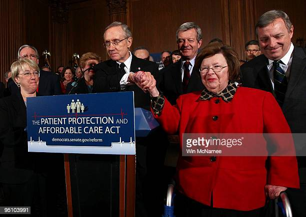 Senate Majority Leader Harry Reid shakes hands with Sen Barbara Mikulski who cast the 60th vote in a final series of procedural votes on pending...