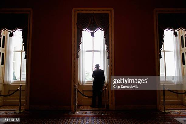 Senate Majority Leader Harry Reid steps out of the weekly Democratic policy luncheon to talk on the phone in the US Capitol November 1 2011 in...
