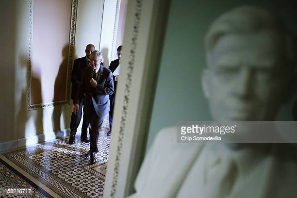 Senate Majority Leader Harry Reid walks out of his party's weekly policy luncheon before talking to reporters at the US Capitol December 11 2012 in...