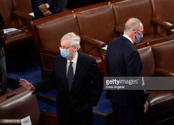 Senate Majority Leader Mitch McConnell and Senate Minority Leader Chuck Schumer stand back to back in the House Chamber during a joint session of...
