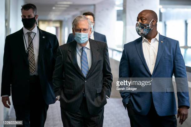 Senate Majority Leader Mitch McConnell and Senator Tim Scott walk to a Republican caucus luncheon in the Hart Senate Office Building on Capitol Hill...