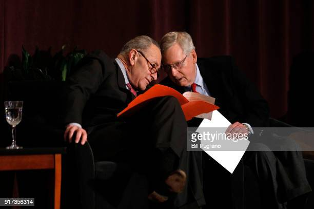 S Senate Majority Leader Mitch McConnell and US Senate Democratic Leader Chuck Schumer speak to each other while waiting on stage at the University...