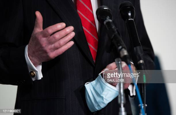 Senate Majority Leader Mitch McConnell , holds a mask to protect himself and others from COVID-19, as he speaks to the media following the weekly...