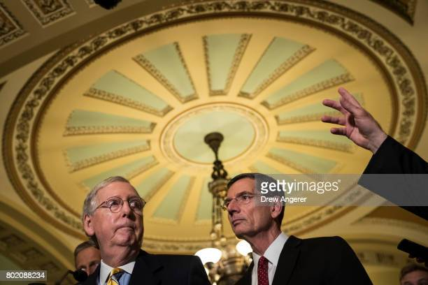 Senate Majority Leader Mitch McConnell listens to a question as Sen John Barrasso looks on during a press conference after a closeddoor Senate GOP...
