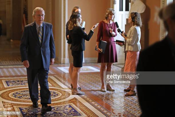 Senate Majority Leader Mitch McConnell walks past Sen Lisa Murkowski as she is interviewed following the GOP weekly policy luncheon at the US Capitol...