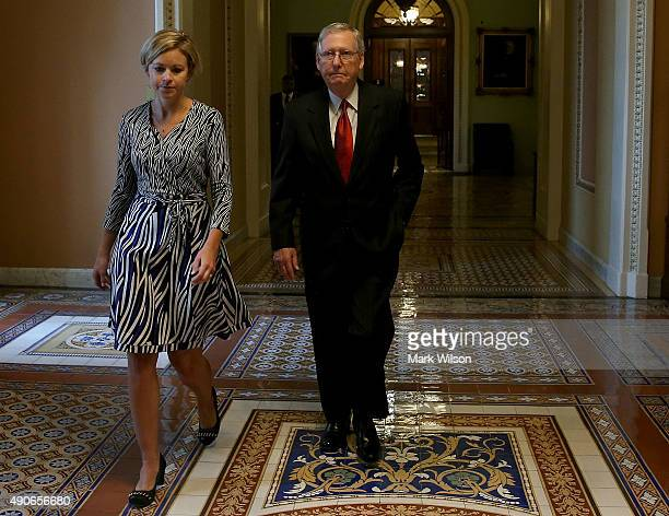 Senate Majority Leader Mitch McConnell walks with an aide as he leaves the Senate Chamber after a vote to avert a government shutdown on Capitol Hill...