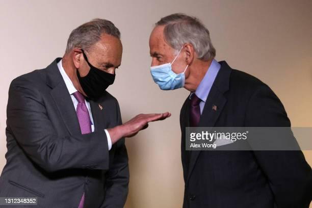 Senate Majority Leader Sen. Chuck Schumer talks to Sen. Tom Carper during a news briefing after a weekly Senate Democratic Policy Luncheon at Hart...