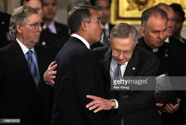 S Senate Majority Leader Sen Harry Reid hugs Speaker of the House Rep John Boehner as Senate Minority Leader Sen Mitch McConnell looks on as Senator...