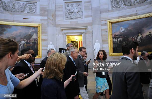 S Senate Majority Leader Sen Harry Reid tries to make his way through photographers and journalists while returning to his office after meeting with...