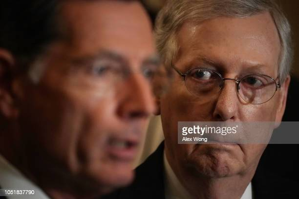 S Senate Majority Leader Sen Mitch McConnell listens as Sen John Barrasso speaks during a news briefing after a weekly Senate Republican policy...