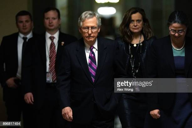 Senate Majority Leader Sen. Mitch McConnell walks towards the Senate chamber with aides after the House passed a bill to temporary fund the...