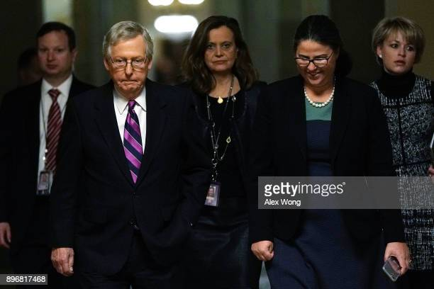 S Senate Majority Leader Sen Mitch McConnell walks towards the Senate chamber with aides after the House passed a bill to temporary fund the...
