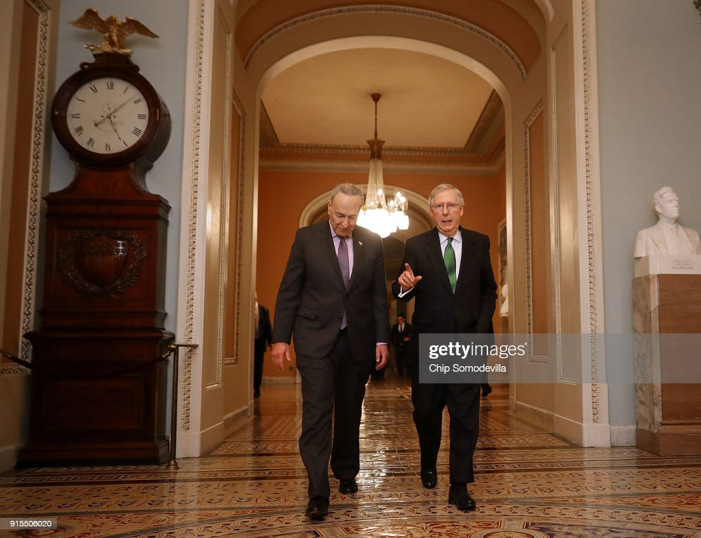 Senate Major Leader McConnell (R-KY) And Senate Minority Leader Schumer (D-NY) Walk To Senate Chamber Together After Budget Deal Reached : News Photo