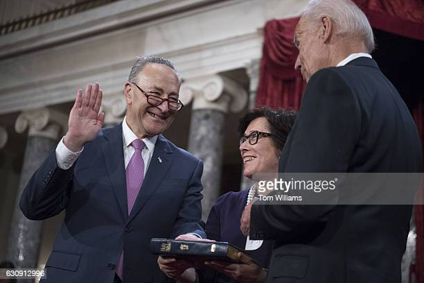Senate Minority Leader Charles Schumer DNY is administered an oath as his wife Iris Weinshall looks on by Vice President Joe Biden during swearingin...