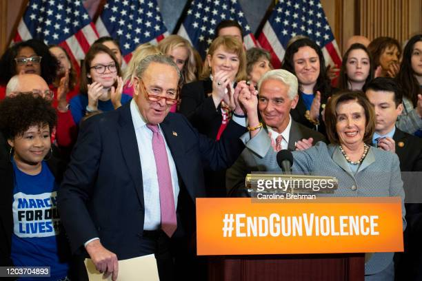 Senate Minority Leader Chuck Schumer, D-N.Y., left, and Speaker of the House Nancy Pelosi, D-Calif., with fellow Democrats and members of Moms Demand...