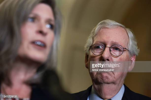 Senate Minority Leader Mitch McConnell listens as Sen. Joni Ernst addresses reporters following a weekly Republican policy meeting at the U.S....