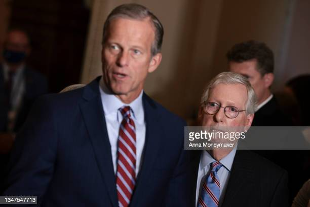 Senate Minority Leader Mitch McConnell listens as U.S. Senate Minority Whip Sen. John Thune speaks to reporters following a weekly Republican policy...