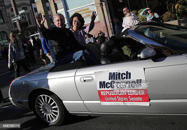 Senate Minority Leader Mitch McConnell waves while riding with his wife Elaine Chao in the Hopkins Country Veterans Day Parade on November 2 2014 in...