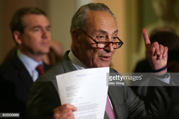 S Senate Minority Leader Sen Chuck Schumer speaks as Sen Michael Bennet looks on during a media briefing at the Capitol August 1 2017 in Washington...