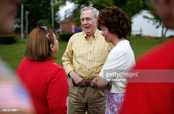 Senate Minority Leader Sen Mitch McConnell and his wife Elaine Chao talk with a voter after riding in the Adairville Strawberry Festival parade while...