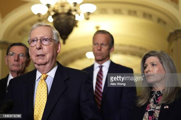 Senate Minority Leader Sen. Mitch McConnell speaks as Sen. John Barrasso , Senate Minority Whip Sen. John Thune and Sen. Joni Ernst listen during a...