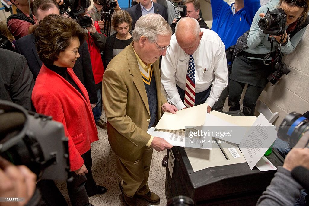 Senate Minority Leader U.S. Sen. Mitch McConnell (R-KY) prepares to cast his vote in the midterm elections as his wife Elaine Chao watches at Bellarmine University November 4, 2014 in Louisville, Kentucky. McConnell is running in a tight race against opponent Kentucky Secretary of State Alison Lundergan Grimes.