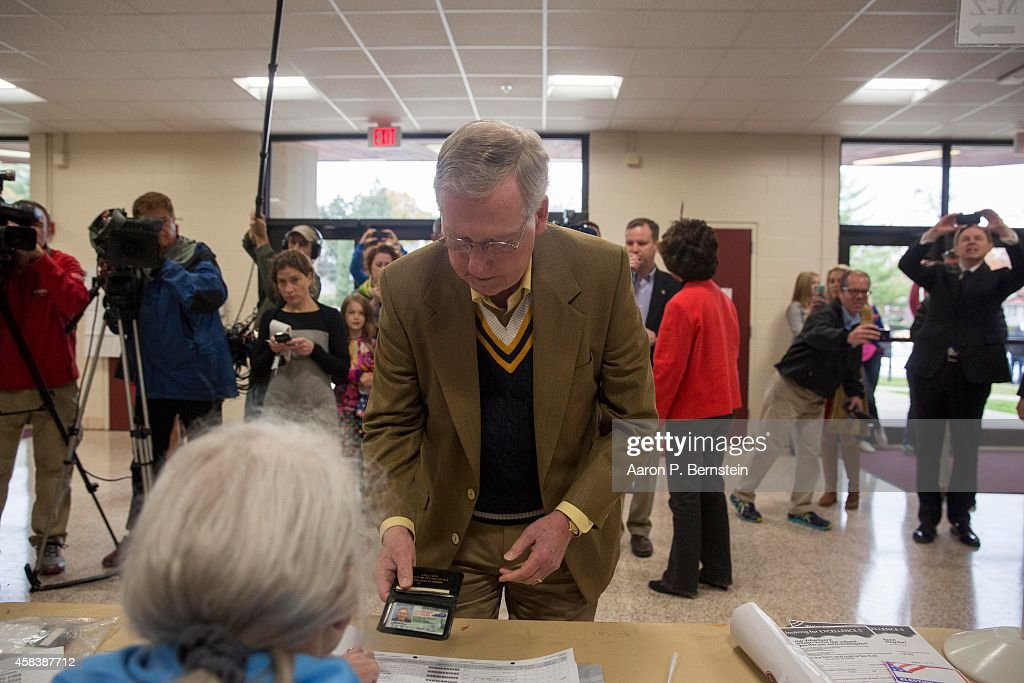 Senate Minority Leader U.S. Sen. Mitch McConnell (R-KY) presents his identification to vote in midterm elections at Bellarmine University November 4, 2014 in Louisville, Kentucky. McConnell is running in a tight race against opponent Kentucky Secretary of State Alison Lundergan Grimes.